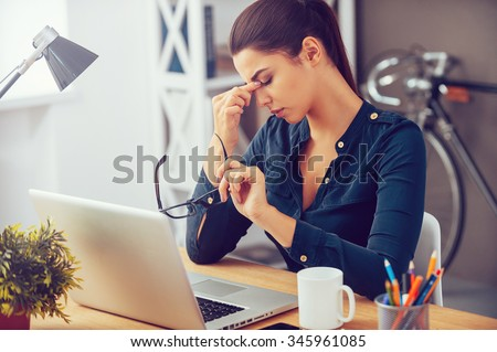 Feeling tired and stressed. Frustrated young woman keeping eyes closed and massaging nose while sitting at her working place in office - stock photo