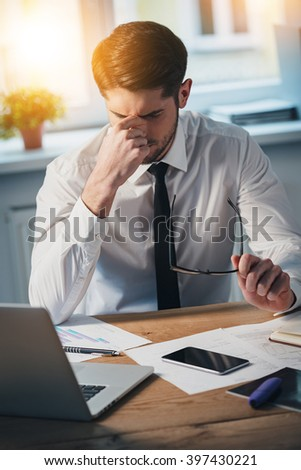 Feeling tired. Frustrated young handsome man looking exhausted while sitting at his working place  - stock photo