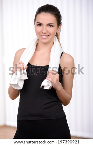 Feeling young and healthy. Beautiful woman in sports clothing holding towel on shoulders and smiling - stock photo