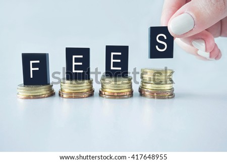Fees text stacked on coins with cool image temperature  - stock photo