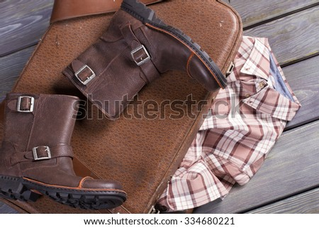 Fees tourist in travel. Old suitcase, leather boots and a checkered shirt.