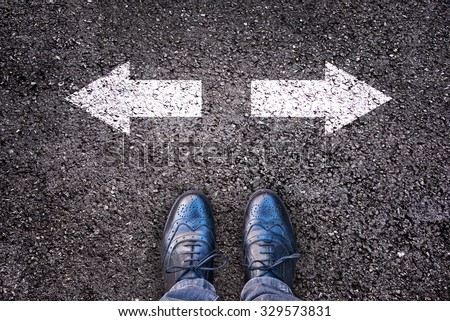 Feet and two arrows painted on an asphalt road - stock photo