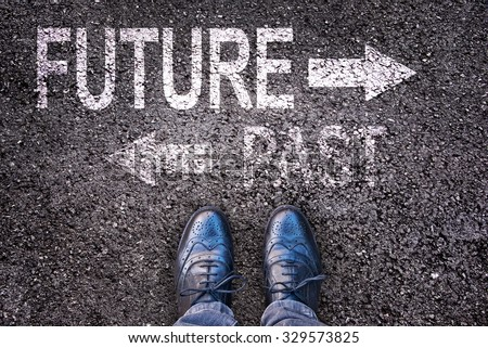 Feet and words future and past painted on an asphalt road - stock photo