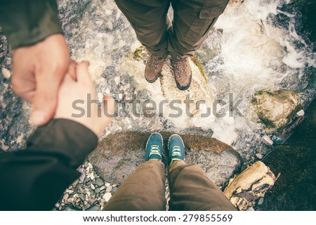 Feet Couple Man and Women in love holding hands hiking outdoor Lifestyle Travel and relationship concept river and stones on background top view - stock photo