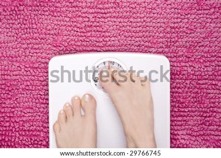 Feet cringing on scales, shot landscape. - stock photo