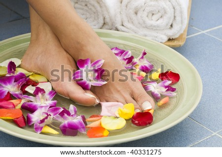 Feet enjoy a relaxing aromatherapy foot spa - stock photo