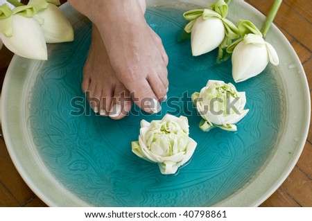 Feet enjoy a relaxing aromatherapy foot spa with Lotus flowers - stock photo
