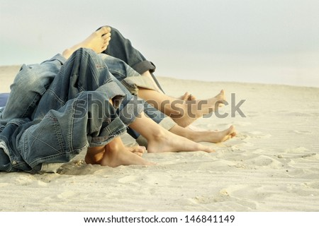 feet four persons lying on the sand - stock photo