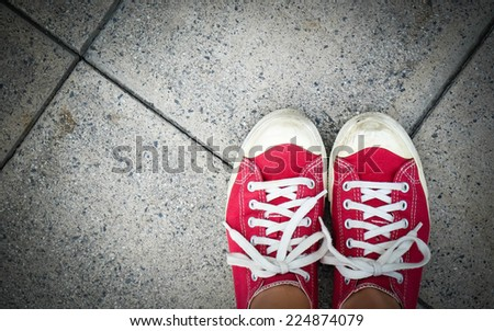 Feet in red canvas sneaker on concrete floor, top view - stock photo