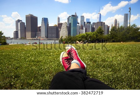 Feet in red sneakers in green grass in front of Manhattan, New York - stock photo