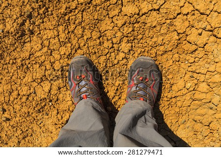 Feet in sneakers on the background of cracked earth. - stock photo