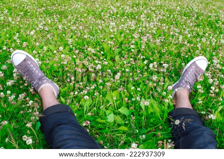 feet in sneakers on the green grass