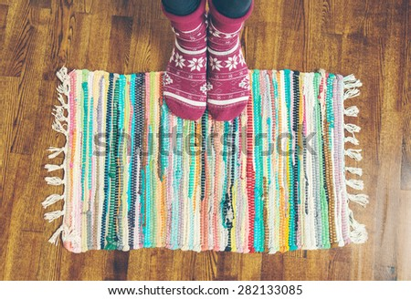 Feet in socks on a wooden floor and a traditional color carpet in home interior in winter - stock photo