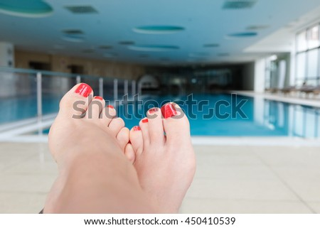 Feet in the swimming pool. Relax, vacation, summer. Red nails, suntanned skin, turquoise water.