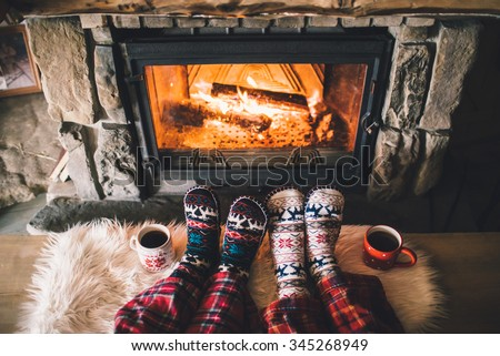 Feet in woollen socks by the Christmas fireplace. Couple sitting under the blanket, relaxes by warm fire and warming up their feet in woollen socks. Winter and Christmas holidays concept. - stock photo