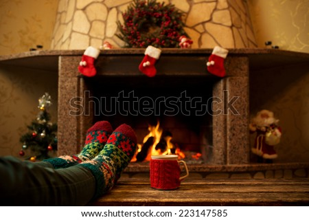 Feet in woollen socks by the Christmas fireplace. Woman relaxes by warm fire with a cup of hot drink and warming up her feet in woollen socks. Close up on feet. Winter and Christmas holidays concept.  - stock photo
