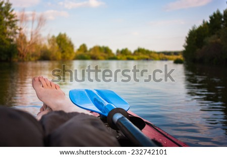 Feet luing on kayak in river summer landscape with trees and clouds  - stock photo