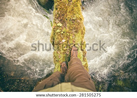 Feet Man trekking boots hiking outdoor with river and stones on background Lifestyle Travel survival concept top view - stock photo