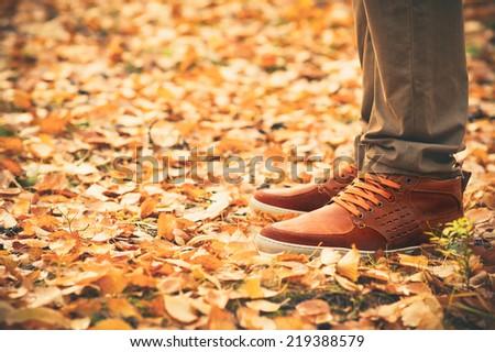 Feet Man walking on fall leaves Outdoor with Autumn season nature on background Lifestyle Fashion trendy style - stock photo
