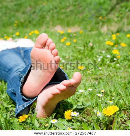 Feet of a beautiful young woman resting in spring time, closeup photo - stock photo