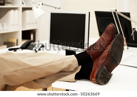 Feet of a businessman on the table in his office - stock photo
