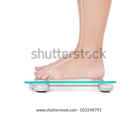 Feet of a female person standing on weight scale. All on white background. - stock photo