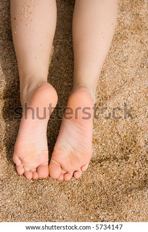 Feet of a girl in the sand - stock photo