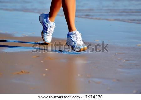 feet of a girl running on the beach - stock photo