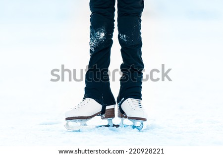 feet of a little girl in skates on ice - stock photo