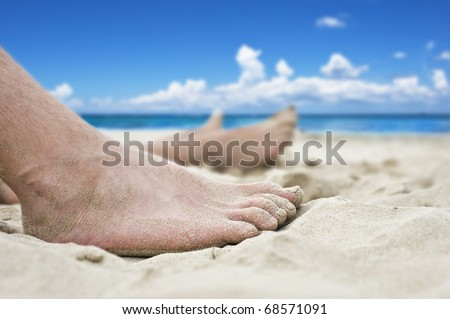 Feet of a man and woman lying on the beach - stock photo