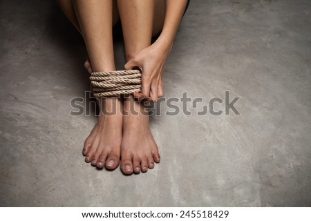 Feet of a missing kidnapped, abused, hostage, victim woman tied up with rope in emotional stress and pain, afraid, restricted, trapped, call for help, struggle, terrified, locked in a cage cell. - stock photo