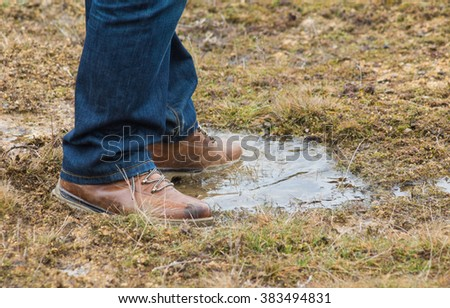 Feet of a person wearing lace up shoes and blue denim jeans standing in a puddle of water in short scrubby grass.
