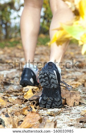 Feet of a runner running in autumn leaves, training for marathon and fitness,  Close-up