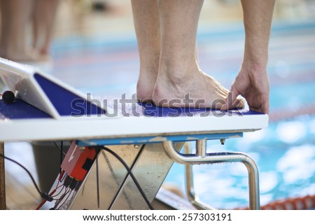 Feet of a swimmer on diving platform - stock photo
