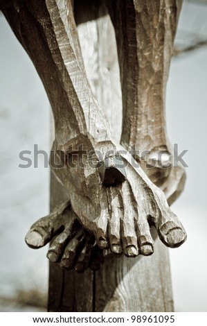 Feet of a wooden jesus christ on the cross - stock photo