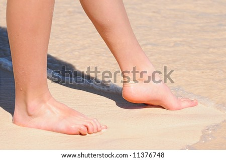 Feet of a young woman touching water on tropical beach