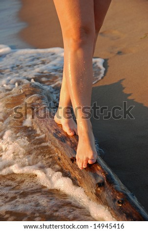Feet of a young woman walking on the log
