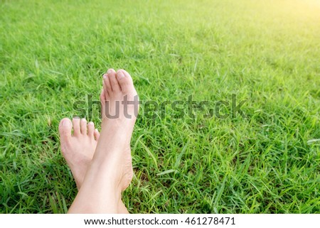 Feet of asian woman relaxing on grass field. Relaxing concept.