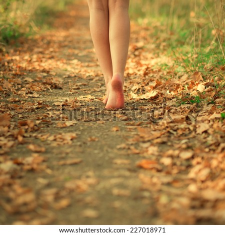 feet of beautiful hipster girl on autumn road - stock photo