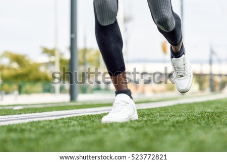 Feet of black man starting running in urban background. Male doing workout outdoors.