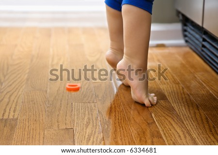 Feet of Caucasian toddler boy with magnets in front of refrigerator. - stock photo
