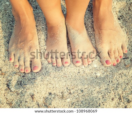 feet of child and mom in the sea sand - stock photo