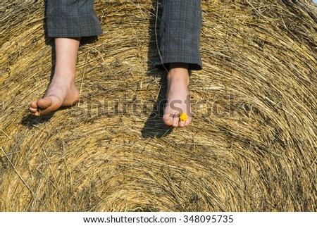 Feet of child boy sitting on haystack / hay bale, summer, relaxing - stock photo