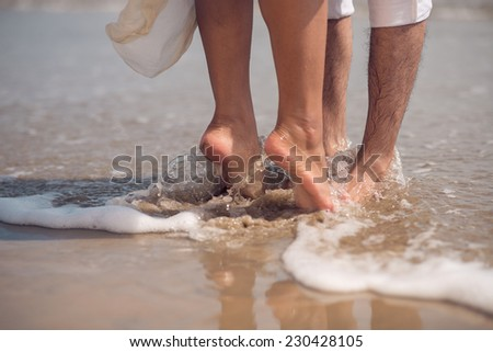 Feet of couple kissing on the beach - stock photo