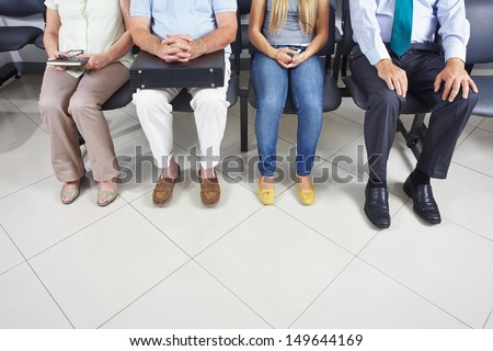 Feet of different people sitting in a waiting room - stock photo