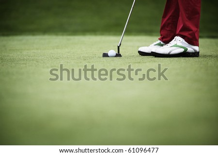Feet of female golf player putting at green, with plenty of copy-space. - stock photo