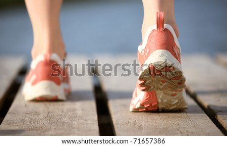 Feet of female running to water - stock photo