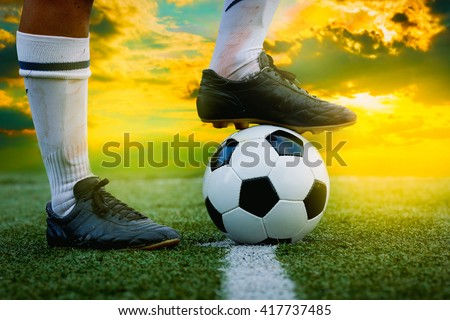 feet of football player tread on soccer ball for kick-off - stock photo