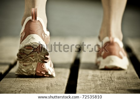 Feet of jogging man. Vintage tinted image - stock photo