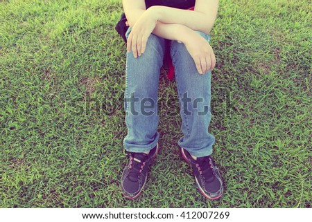 Feet of lonely hipster sitting alone. Cropped portrait of young girl. Top view of shoes of hipsters resting. - stock photo